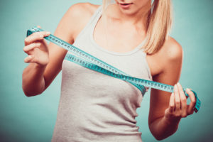 Fitness woman fit girl in sportswear with measure tape measuring her size chest breast on blue-img-blog