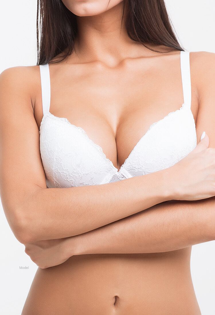 Woman in white bra with arms crossed