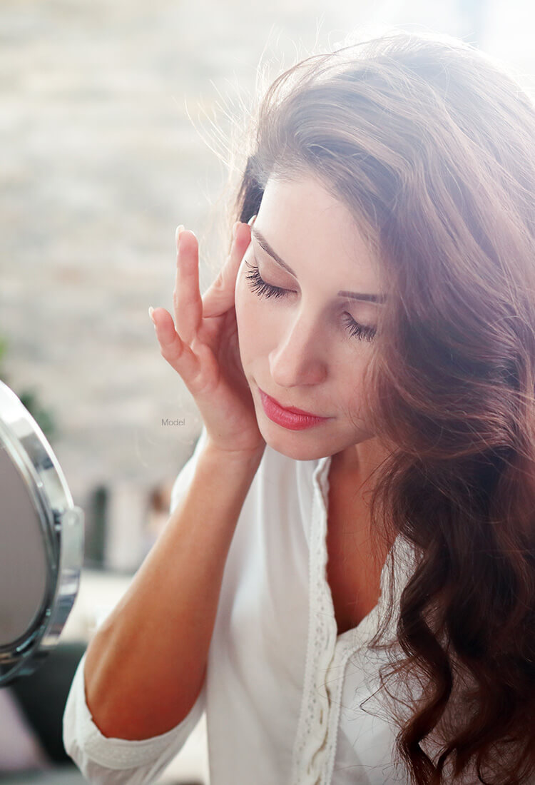 Beautiful woman looking in mirror